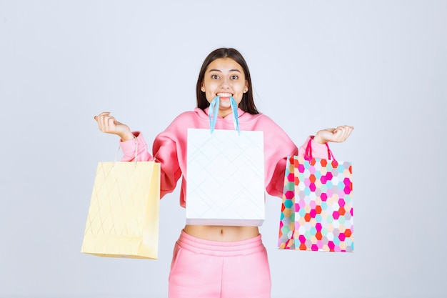 Girl holding colorful shopping bags at her mouth.