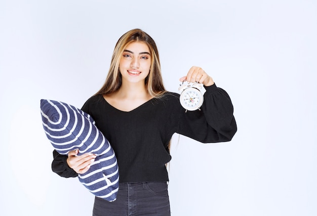 Girl holding a comfy blue pillow and an alarm clock.