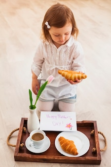 Girl holding croissant near tray with greeting card