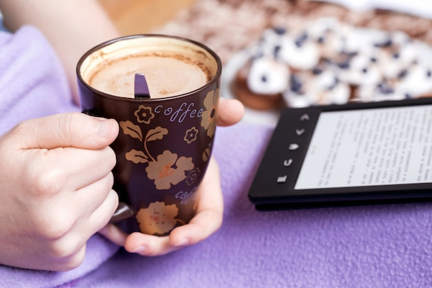 Girl holding a cup of coffee and reading ebook.