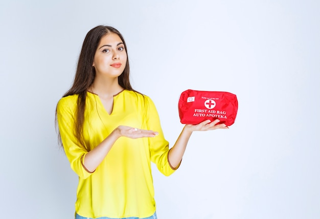 Girl holding and demonstrating a red first aid kit.