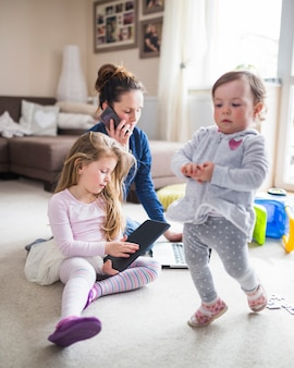 Girl holding digital tablet in front of woman using laptop