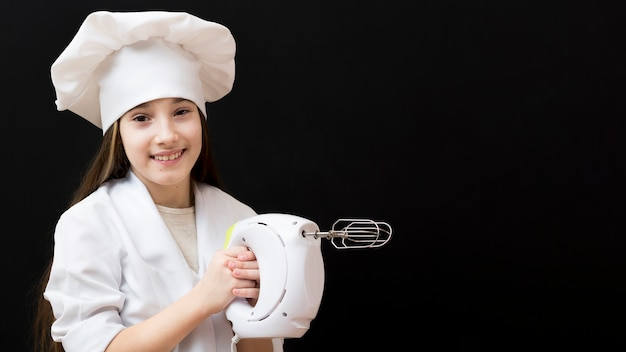 Girl holding electric mixer copy space