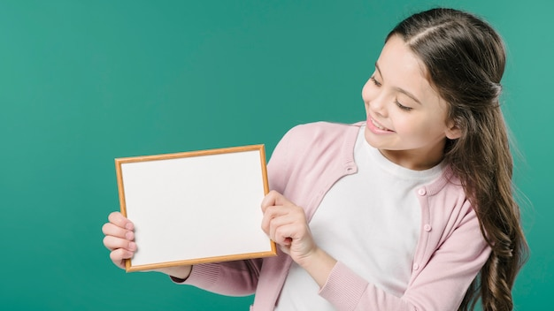 Girl holding empty picture frame