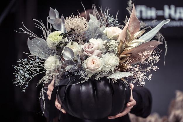 Girl holding a flower arrangement in a pumpkin.
