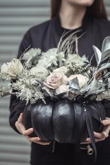 Girl holding a flower arrangement in a pumpkin