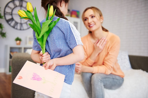 花とグリーティングカードを後ろに持っている女の子