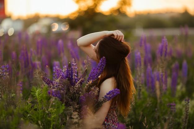 花を持って女の子。フィールドでブルネット。日没