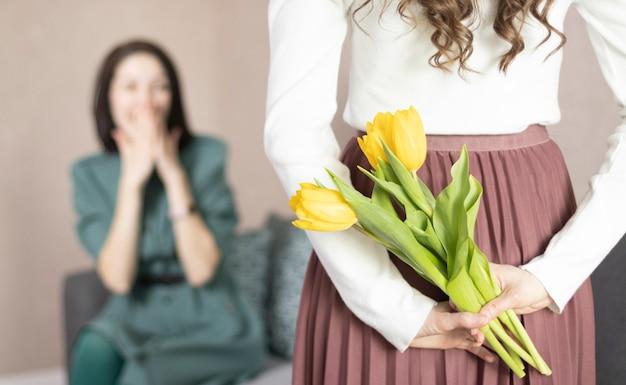 彼女の後ろに母親のための花を保持している女の子、クローズアップ