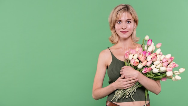 Girl holding flowers and looking at photographer