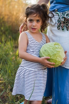 Girl holding fresh harvested cabbage standing with her mother