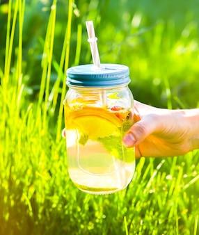 ストローの瓶に新鮮なレモネードを保持している女の子。流行に敏感な夏の飲み物。自然の中で環境にやさしい。ガラスにミントが入ったレモン、オレンジ、ベリー。屋外の緑の高い草。