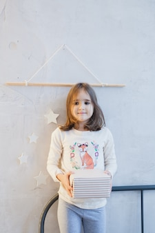 Girl holding gif for new year or christmas, christmas tree and interior decorated for new year, christmas, holiday anticipation