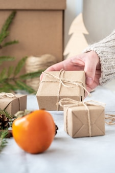 Girl holding a gift packed with her own hands, close-up. christmas decoration, design of a gift box for christmas made of natural materials. new year's atmosphere, preparation for christmas.