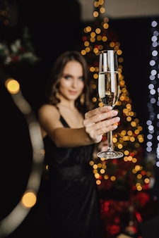 Girl holding a glass with champagne stands in a foreground