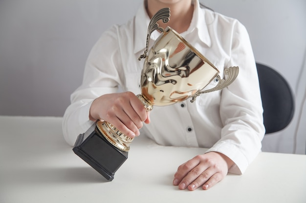 Girl holding golden trophy in office. business, success