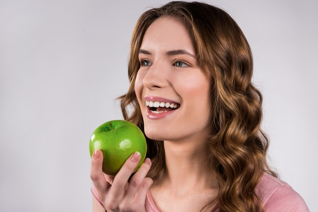 Girl holding green apple smiling isolated.
