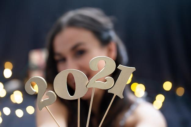 Ragazza che tiene in mano il numero del prossimo anno su uno sfondo sfocato scuro.