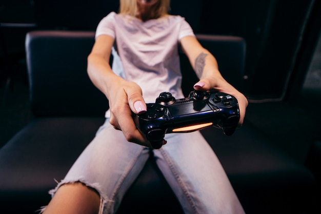 Girl holding in hands gamepad and playing videogames