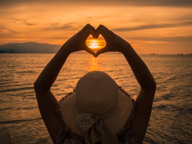 Девушка, держась за руки в форме сердца, обрамляя закатом солнце на закате на океанском пляже