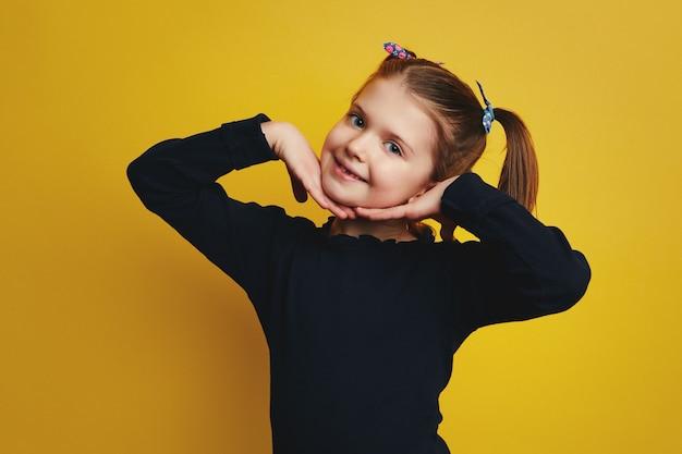 Девушка держит руки на щеках, улыбаясь в камеру, изолированную над желтой стеной