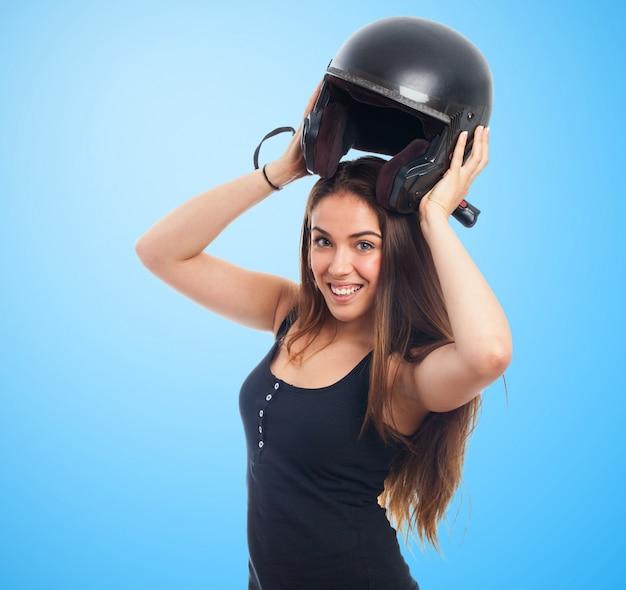Girl holding helmet over head