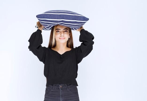 그녀의 파란색 줄무늬 베개를 잡고 잠자는 소녀.