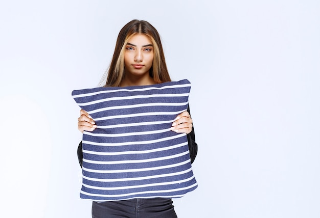 Girl holding her blue striped pillow and sleeping. high quality photo