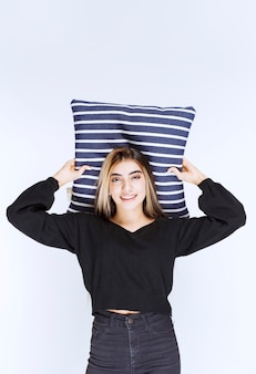 Girl holding her blue striped pillow and sleeping.