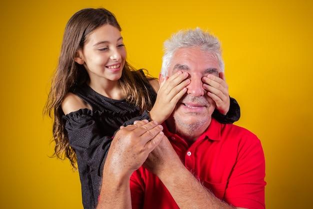 父親を抱いた少女が目を閉じた。黄色の背景。父の日。ブラジルの家族。