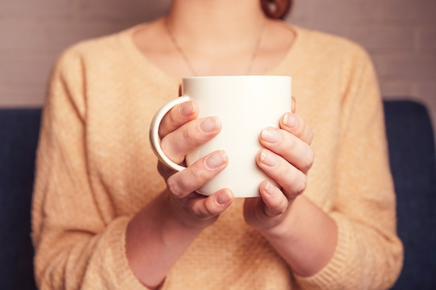 A girl holding in her hands a mug of coffee