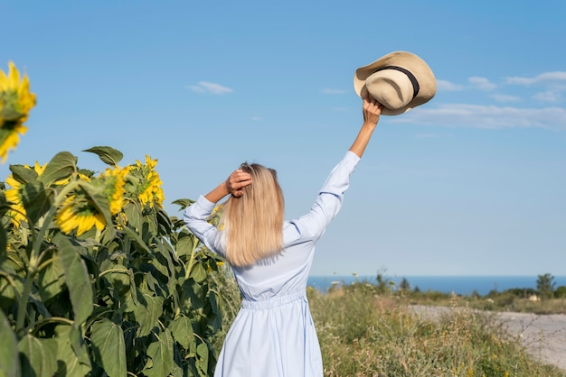 太陽の花のフィールドで彼女の帽子を持ち上げて女の子