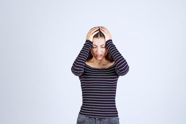 Ragazza che tiene la sua testa perché è stanca o ha mal di testa.