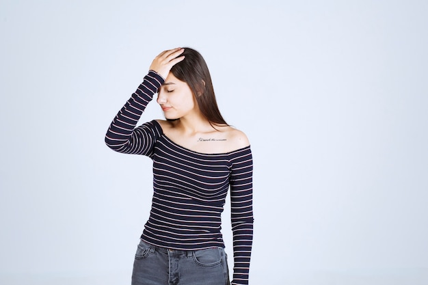 Girl holding her head as she is tired or has headache.