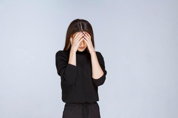 疲れている、または頭痛があるので頭を抱えている女の子。高品質の写真