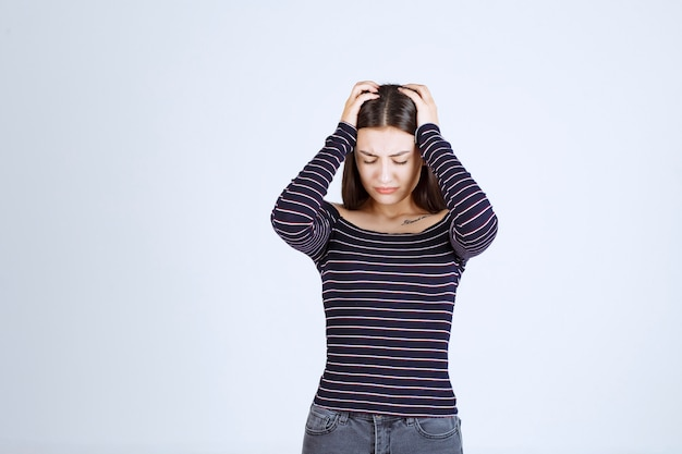 그녀는 피곤하거나 두통이 있기 때문에 그녀의 머리를 잡고 소녀.