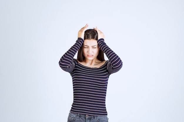 Девушка держится за голову, так как она устала или у нее болит голова.