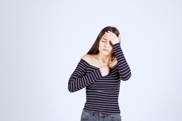 疲れている、または頭痛があるので頭を抱えている女の子。