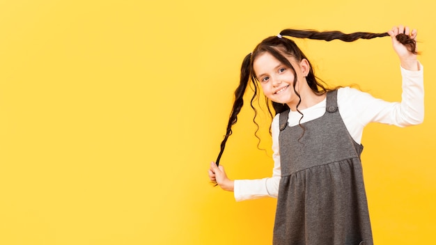 Girl holding her pigtails copy-space