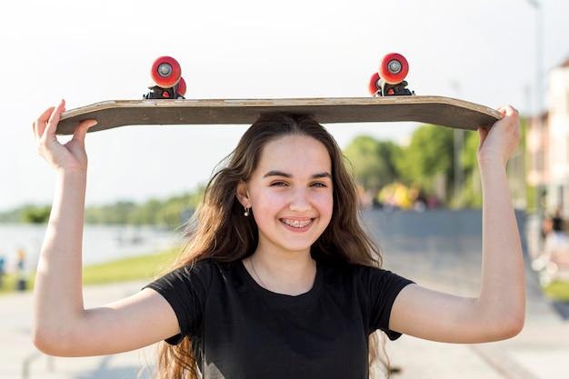 Ragazza che tiene il suo skateboard sulla sua testa fuori