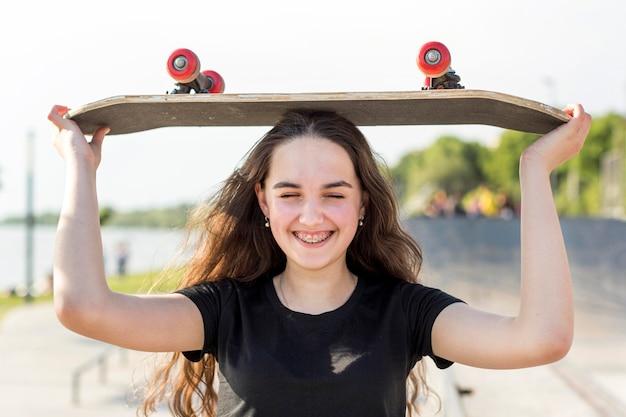 Ragazza che tiene il suo skateboard sulla sua testa
