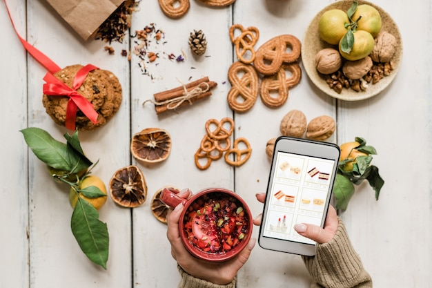 Girl holding hot drink and smartphone while scrolling through goods in online shop over table with xmas snack