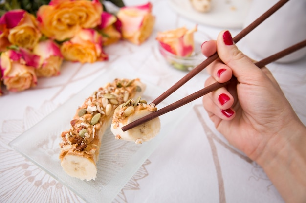ガラス板にナッツとミューズリーとバナナの寿司と日本の棒を手に持っている女の子