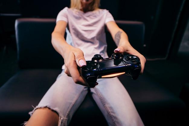 Девушка держит в руках геймпад и играет в видеоигры