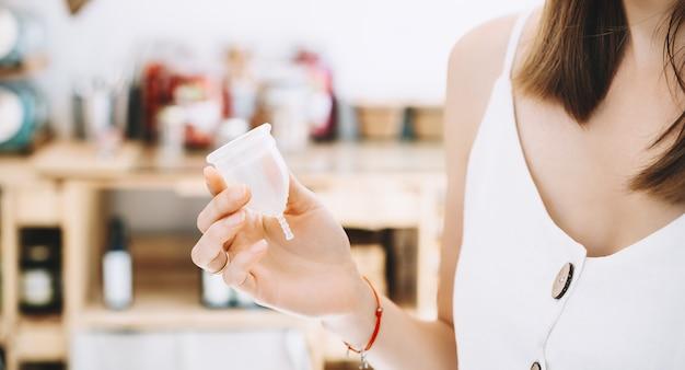 지속 가능한 플라스틱 무료 매장에서 생리컵을 손에 들고 있는 소녀