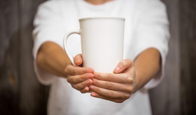 La ragazza con in mano una tazza grande su legno