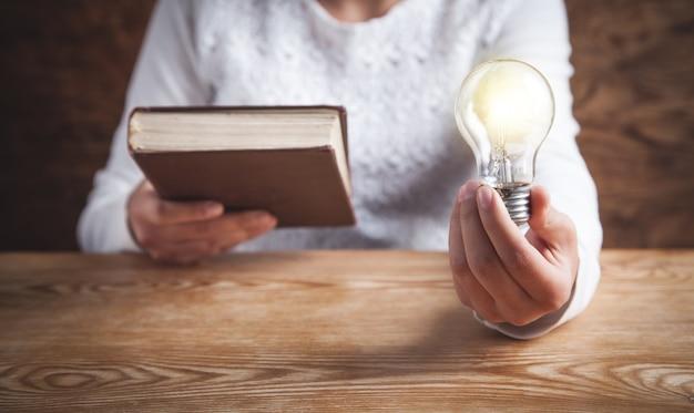 Девушка держит лампочку и книгу. знание, творчество, мудрость