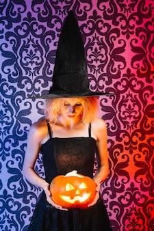 Girl holding lighted pumpkin