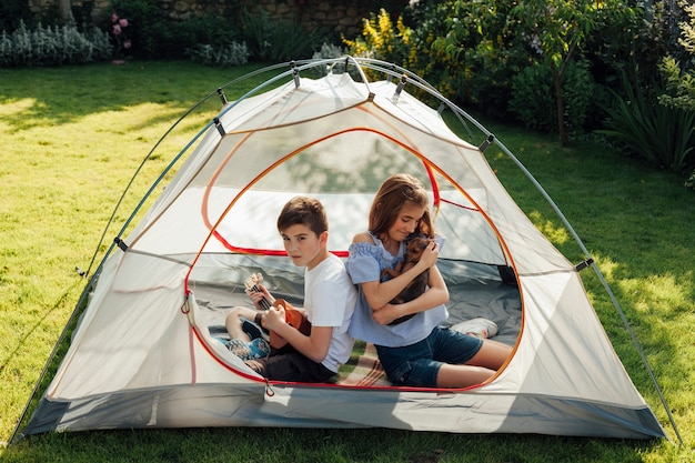 Girl holding little dog sitting with her brother in tent camp in park