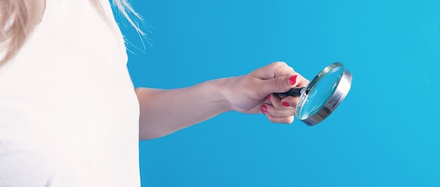 Girl holding a magnifying glass in her hand and looking